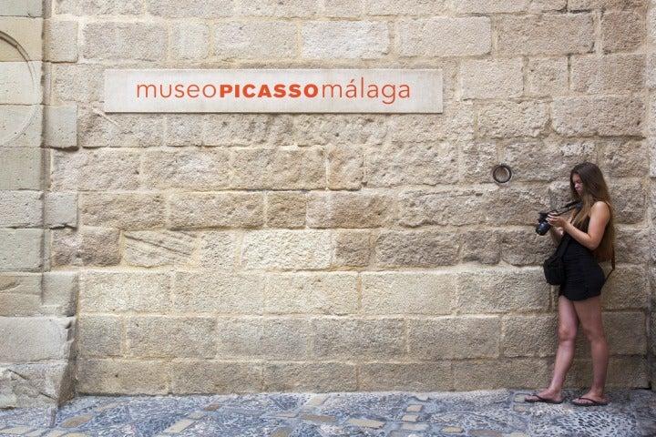 touriste avec un appareil photo devant le musée picasso málaga | entrée musée picasso andalousie espagne