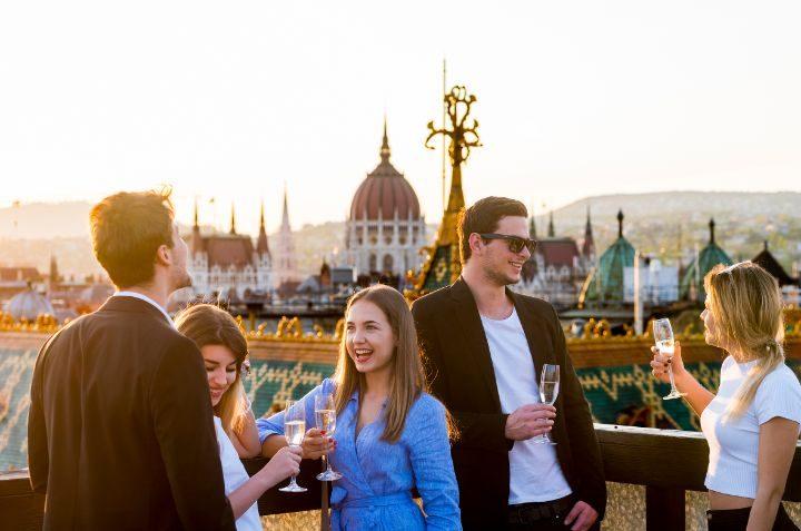 groupe amis buvant un verre au coucher du soleil parlement budapest hongrie